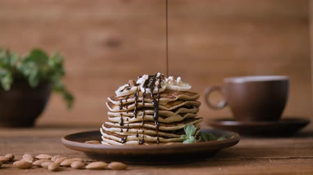 традиционный : Homemade pancakes with banana, almonds and chocolate. Стоковые видеозаписи