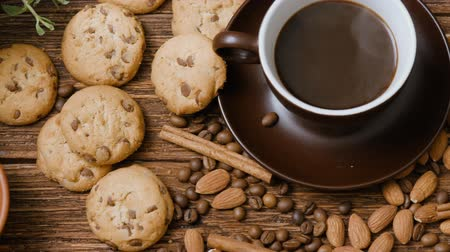 hot beverage : Coffee cup, beans, almond, chocolate and cookie on old kitchen table. Top view. Stock Footage