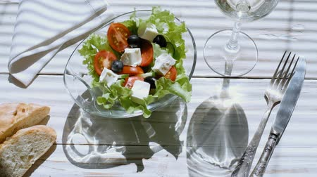 фета : Cinemagraph - Greek salad and a glass of white wine. Motion Photo.