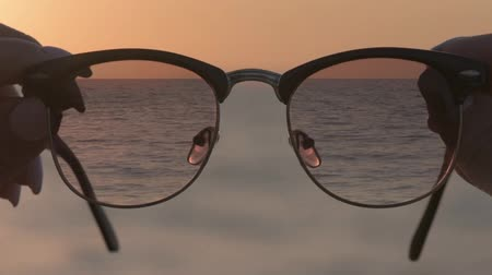 cinemagraph : Cinemagraph - Womans hands holding eyewear, a background of blue sea water. Motion Photo. Stock Footage