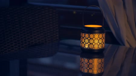 fireflies : Lantern with lighted candle on table with magical lights of fireflies at night. Concept of romance.