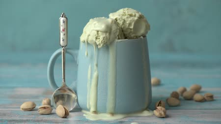 majorság : Cinemagraph - Pistachio ice cream in a cup on a wooden table. Drops of ice cream dripping. Motion Photo.