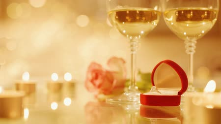 söz : Cinemagraph - Two glasses with white wine and rose flower on bokeh background. Romantic concept. Motion Photo. Stok Video