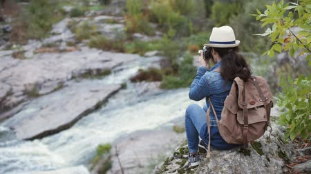 Woman making pictures with a camera while traveling. Natural canyon with view of the mountain river. Concept of travel. Wideo