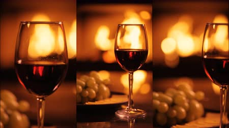 Vertical videos of one red wine wineglasses over fireplace background. Wideo