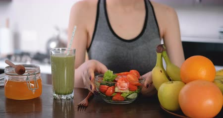 Young woman eating salad after a workout. Wideo