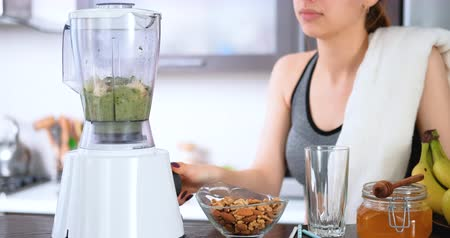 Young woman making green juice with juice machine. Wideo