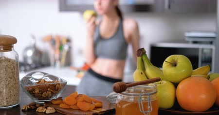 Young woman is eating an apple after a workout.