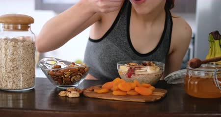 Woman is prepare and eat healthy oatmeal. Wideo