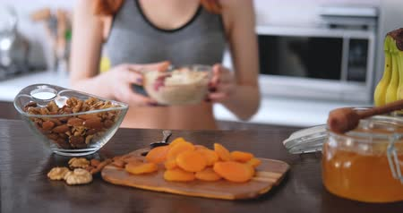 Woman is prepare and eat a healthy oatmeal.