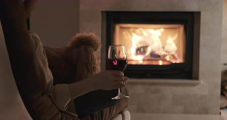 Woman with her dog sitting at home by the fireplace.