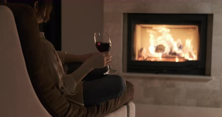 Young woman sitting at home by the fireplace.