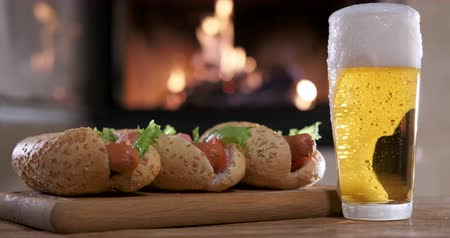 Hotdogs with beer on the fireplace background. Wideo
