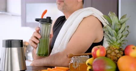 Adult man drinking smoothie in home kitchen after a workout. Dostupné videozáznamy