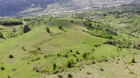 scape : Drone flying above green valley and village, aerial view of hill and village behind