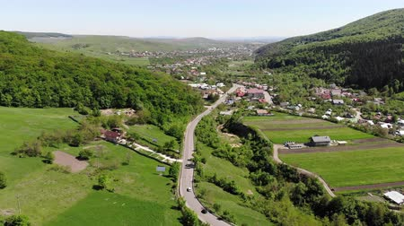 Aerial view of spring country, moving up drone above mountain village road Dostupné videozáznamy