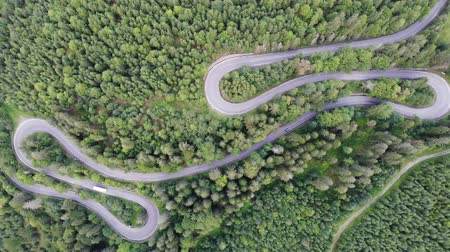 Summer mountain road winding, traffic drone view. Mountain pass through green forest in Romania Dostupné videozáznamy