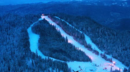 Ski slope and frozen forest in Borsec sports resort, aerial view in the evening. Dostupné videozáznamy