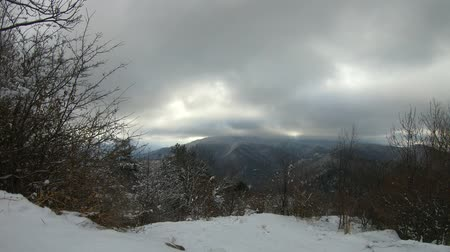 Winter landscape in mountain, time lapse in a winter cloudy day
