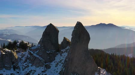Sunset rocky summit, flying drone. Ladys Stones in Rarau mountains, aerial winter panorama of Rarau top.