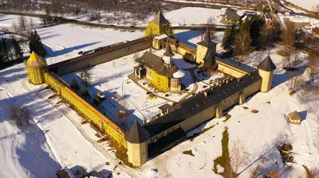 Aerial view of Sucevita monastery in Bukovina. Sucevita monastery was built in 1585 and church paintings date around 1601. The church and surrounding walls are under repair and partial covered in ugly yellow scaffolding,