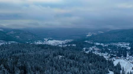 Drone time lapse, Winter sports resort Borsec in Romania, aerial view of frozen forest and resort with some clouds on the sky.