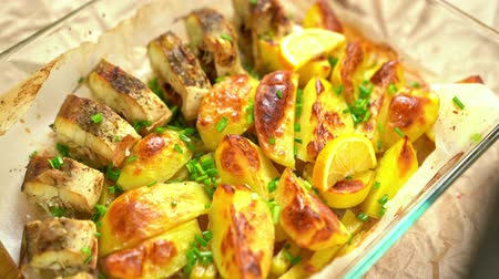 batatas : Cooking Baked fish and potatoes, put a lemon. Stock Footage