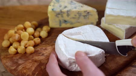 on wooden board round brie cheese cut with a knife Dostupné videozáznamy
