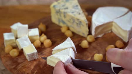 cheese slice : on wooden board triangle cut brie cheese knife Stock Footage