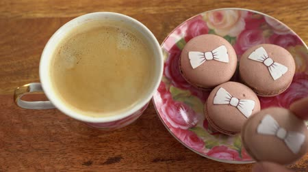 Cup coffee and macaroons, hand takes cake Стоковые видеозаписи