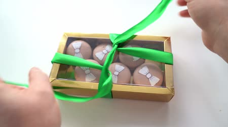 acıbadem kurabiyesi : Untying the green bow on gold box with macaroons. Stok Video