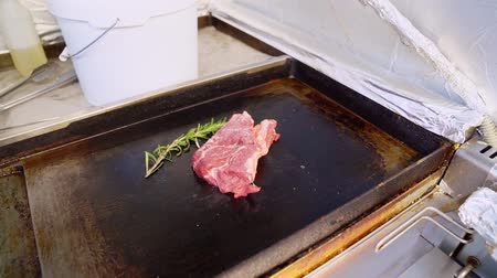 cordeiro : On hot plate is a piece of beef and put a rosemary