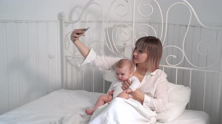 mumie : mum with baby bed taking selfies on smartphone