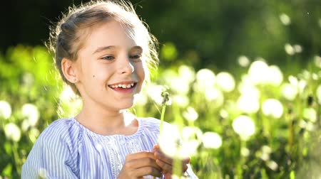 pampeliška : Beautiful little girl at sunny summer day blowing dandelion on green meadow. Summer fun concept. Slow motion. Dostupné videozáznamy