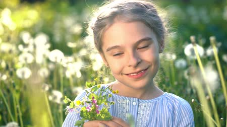 pampeliška : Beautiful little girl at sunny summer day playing with flowers on green meadow. Summer fun concept.
