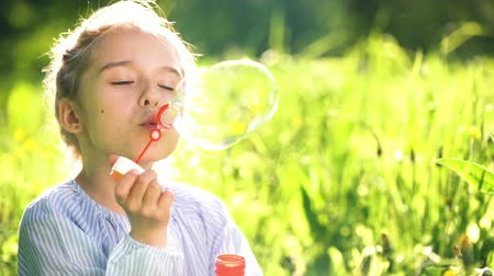 sen : Beautiful little girl at sunny summer day blowing soap bubbles green meadow. Summer fun concept. Slow motion.