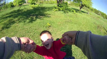 вокруг : Father spinning his happy son on green lawn in park, slow motion, POV Стоковые видеозаписи
