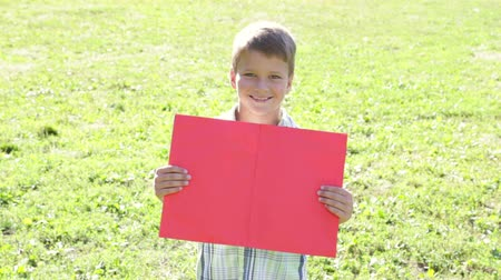 holding : Smiling boy standing with empty blank banner