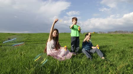 kopec : Three kids blowing up the soap bubbles on the hill