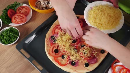 ralado : Three kids adding the grated cheese to raw pizza