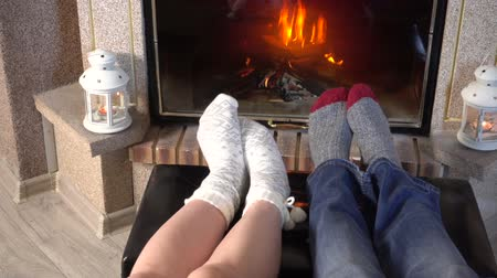 sock : Moving legs of couple in woolen socks heat up near fireplace