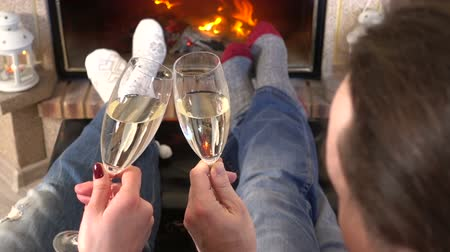 прижиматься : Couple toasting of champagne heating feet together near fireplace