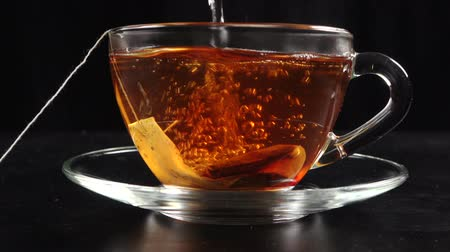 tea bag : Pouring a tea in transparent cup with hot water and teabag, slow motion