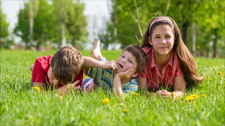 boso : Three kids lying together on green meadow