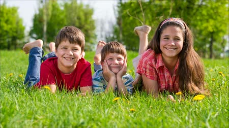 çim : Three kids lying together on green grass meadow Stok Video