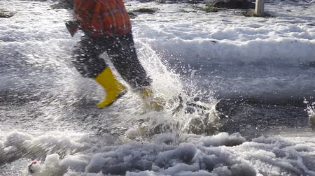 muddy : Kid legs running at the spring creek with melting ice Stock Footage