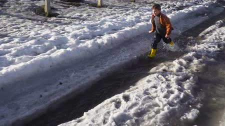 gumboots : Kid running at the spring creek with melting ice