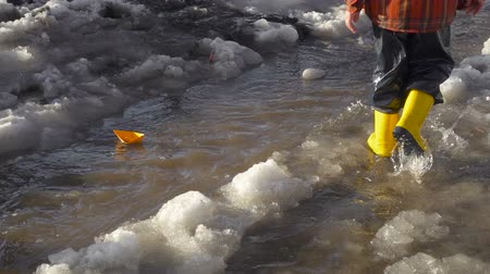 gumboots : Little boy launches a paper boat at the spring creek