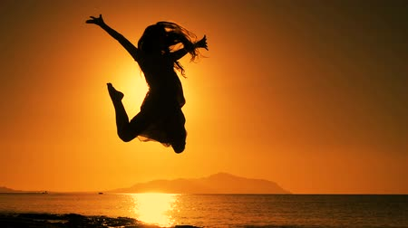 um : silhouette of girl jumping at sunrise Stock Footage