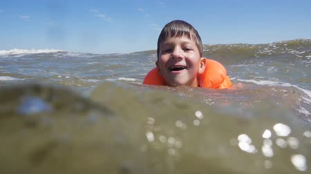 мутный : boy in lifejacket swim in sea with waves